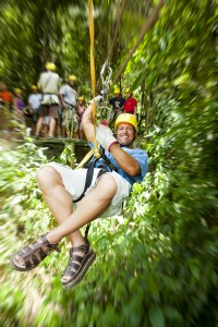 Excited adult man in-motion on zipline in tropical jungle rainfo
