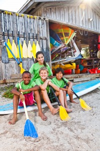 Camp counselor with boys at water sports equipment shack