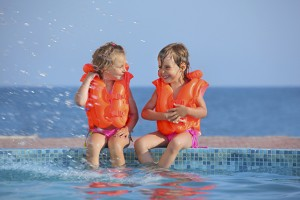 two little girls in lifejackets sitting on ledge pool on resort,