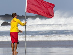 stock-photo-17879643-rnli-lifeguard-puts-out-red-flag