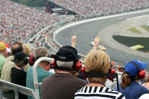 A DSLR photo of a couple of senior fans at a racing event. There is a crowd of people, the stadium is full and there is racing cars on the track. Some people are wearing headsets. There is also one person with arms raised in the air enjoying the race.