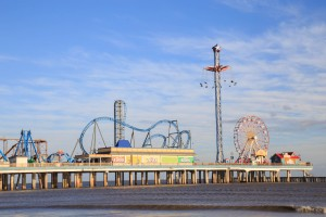 Galveston, USA - January 10, 2016: Historic Pleasure Pier amusement park and beach on the Gulf of Mexico coast in Galveston, Texas.