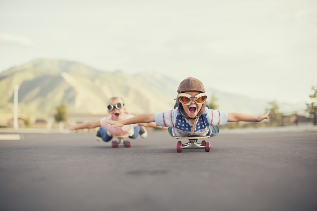 A young boy and girl are wearing flying goggles while outstretching their arms to attempt flying while on skateboards. They have large smiles and are imagining taking off into the sky.