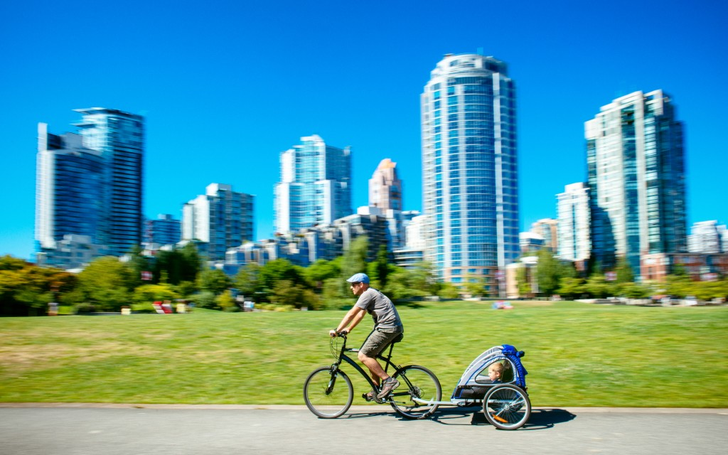 Father carries son in bicycle trailer in Vancouver Canada