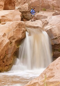 Backpacker Standing Above Waterfall In Capitol Reef National Park