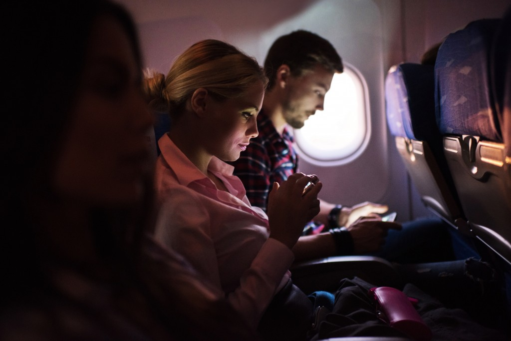 Woman using smart phone in airplane.