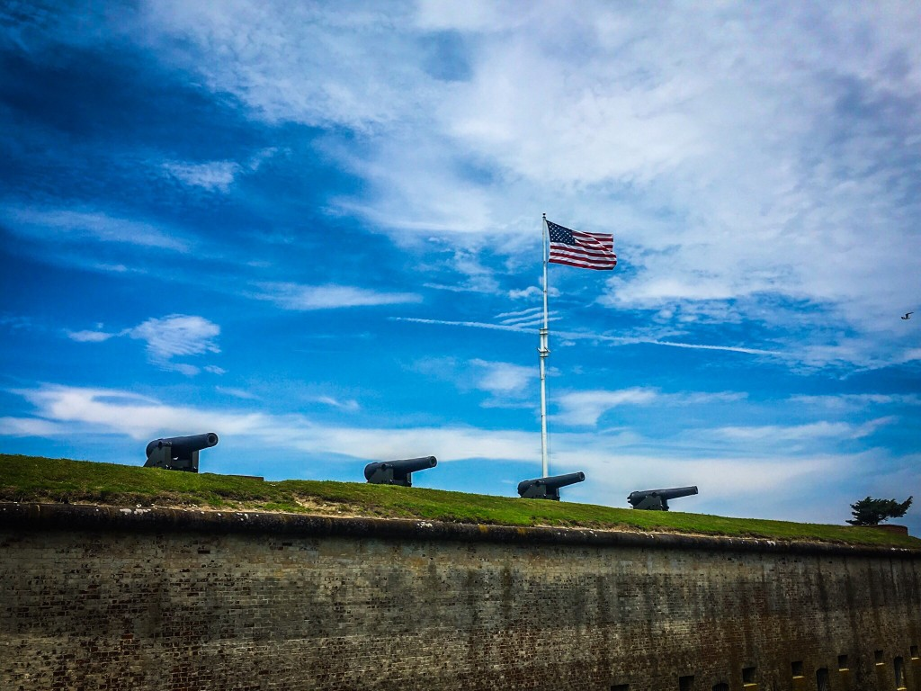 Four cannons atop the eastern wall of Fort Macon with the American flag flying behind.