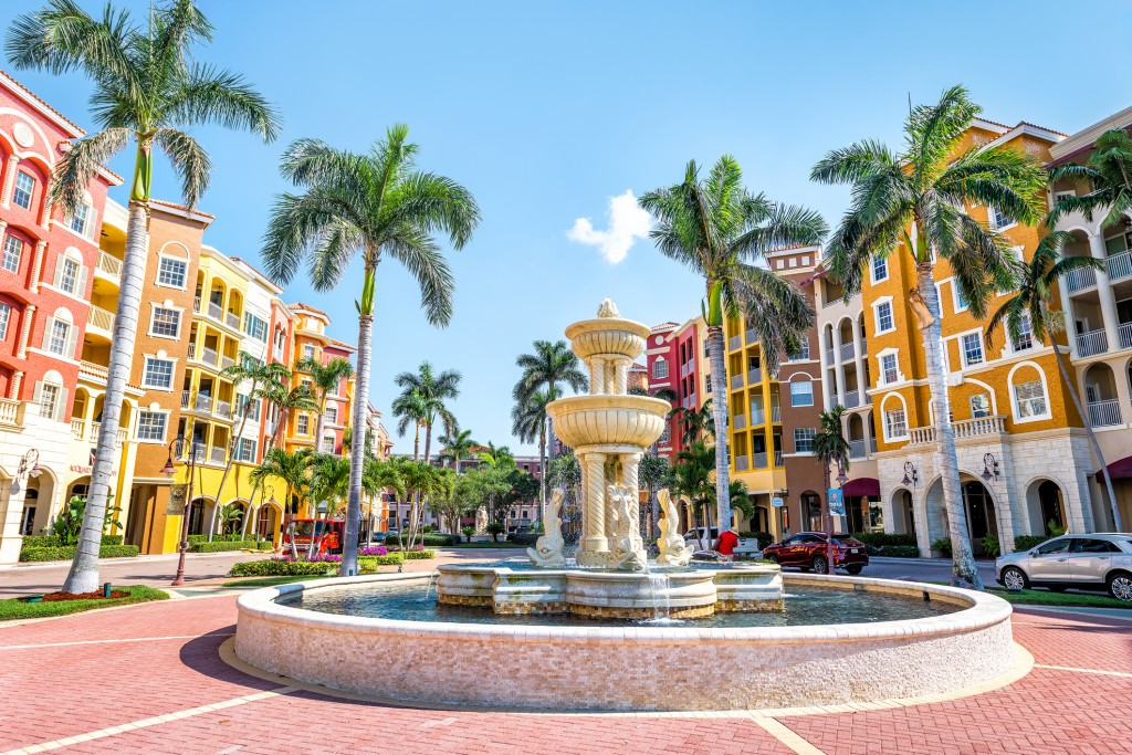 Bayfront condos, condominiums colorful, multicolored, multi-colored buildings with fountain, water, palm trees, blue sky in residential community
