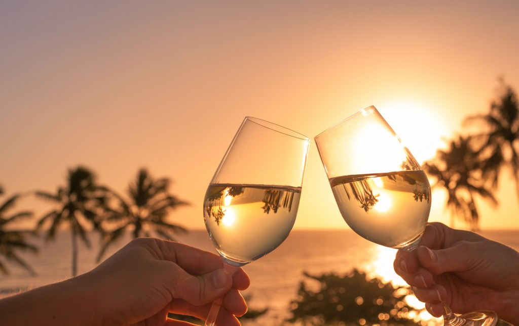 Cheers with wine glasses in a beautiful sunset setting
